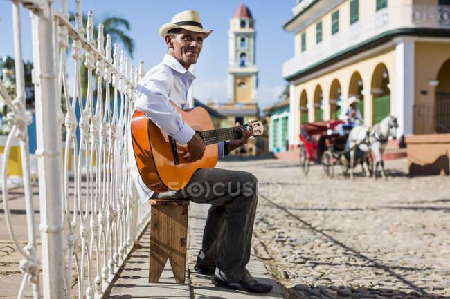 Musiker spielt Gitarre Sittung in der Straße von Trinidad, Kuba — Stockfoto