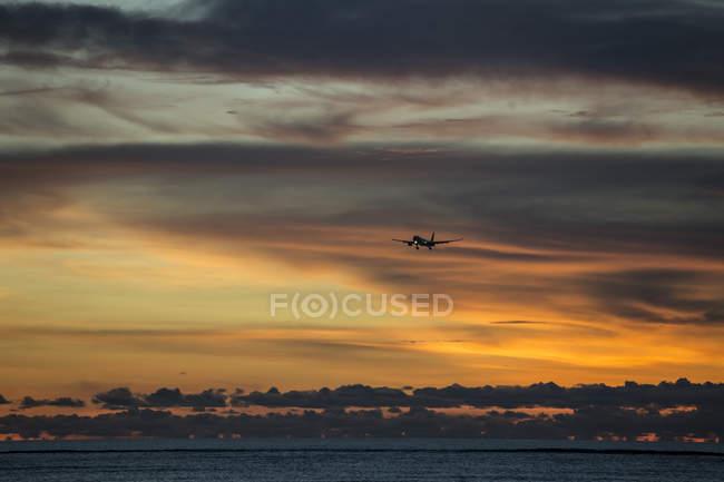Индонезия, Бали, самолет в небе и закат над океаном — стоковое фото