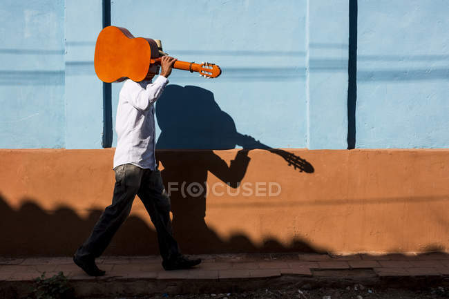 Musician walking with guitar in the street of Trinidad, Cuba — Stock Photo