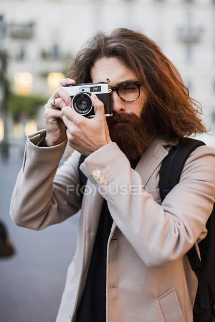Hombre tomando fotos con la cámara antigua - foto de stock