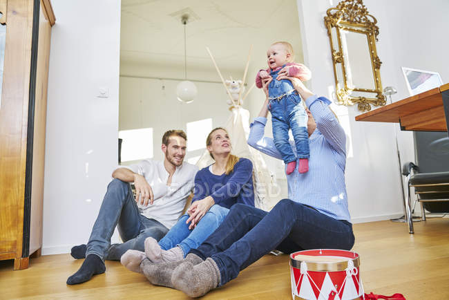 Happy family with baby girl playing in living room — Stock Photo