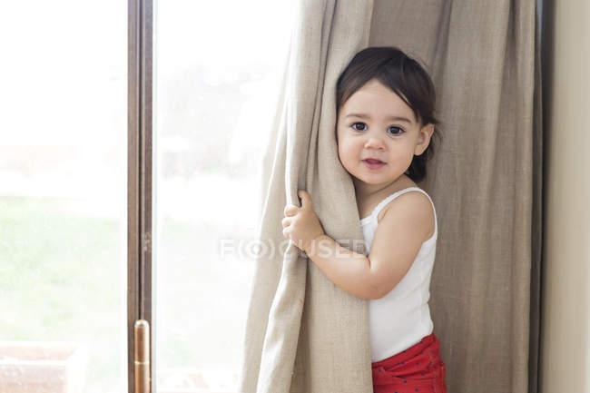 Retrato de uma menina da criança brincando de esconde-esconde por trás das cortinas — Fotografia de Stock