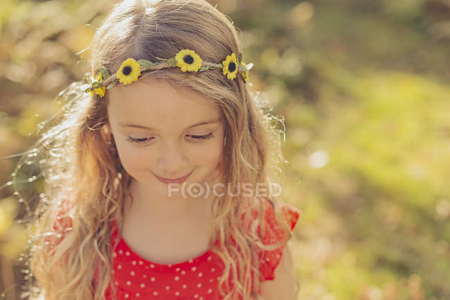Retrato de menina sorridente usando a grinalda da flor — Fotografia de Stock