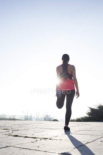 Молода жінка розтягування перед запуском у контуром — стокове фото