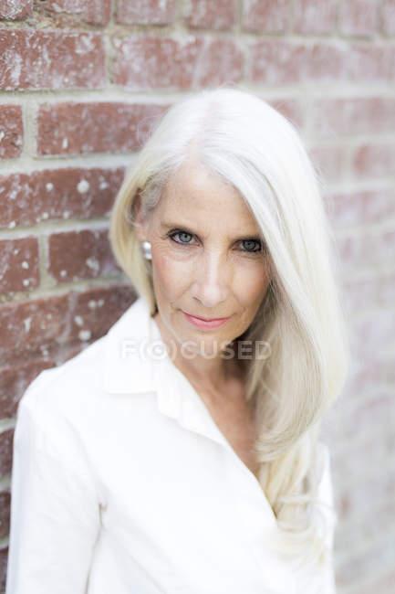 Portrait of senior woman standing near brick wall — Stock Photo