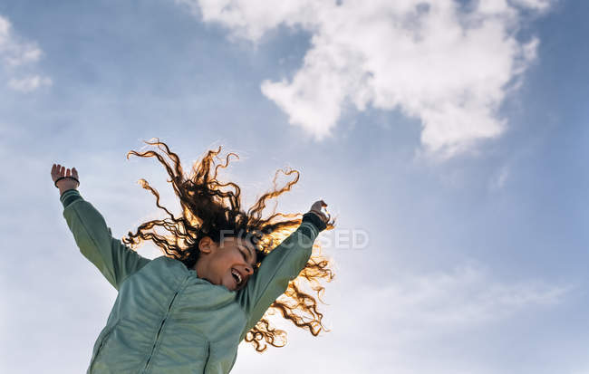 Cute little girl jumping in the air under blue sky — Stock Photo