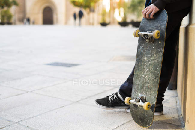Skater boy holding skateboard low section — Stock Photo