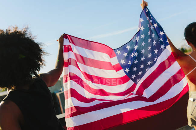 Portrait of young women holding American flag — Stock Photo