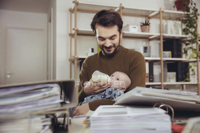 Батько годування свою дитину в домашньому офісі — стокове фото