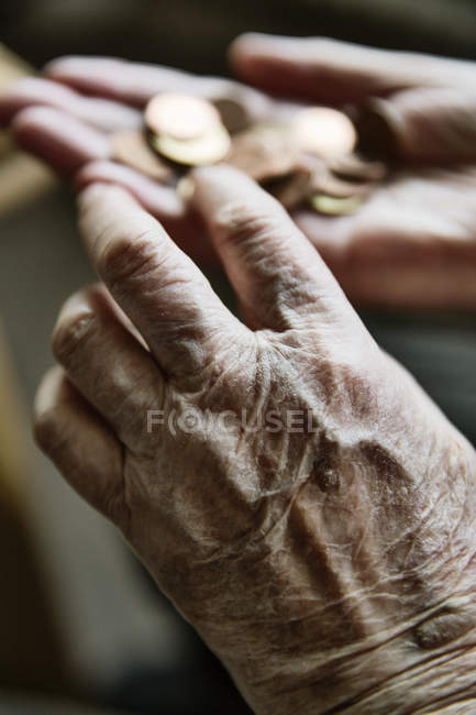 Senior woman's hands with coins — Stock Photo