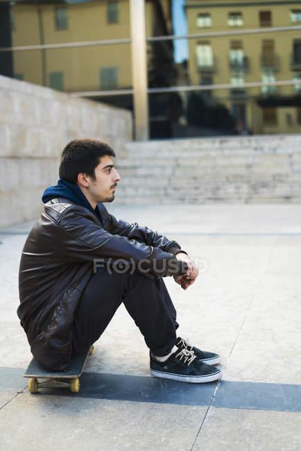 Vista lateral do jovem sentado no skate pela rua — Fotografia de Stock