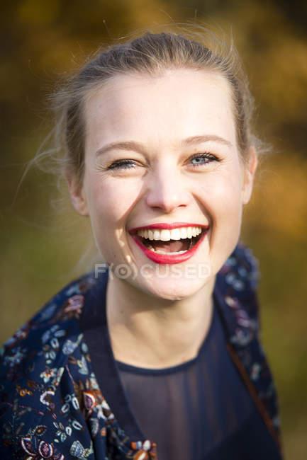 Улыбающаяся молодая блондинка на улице — стоковое фото
