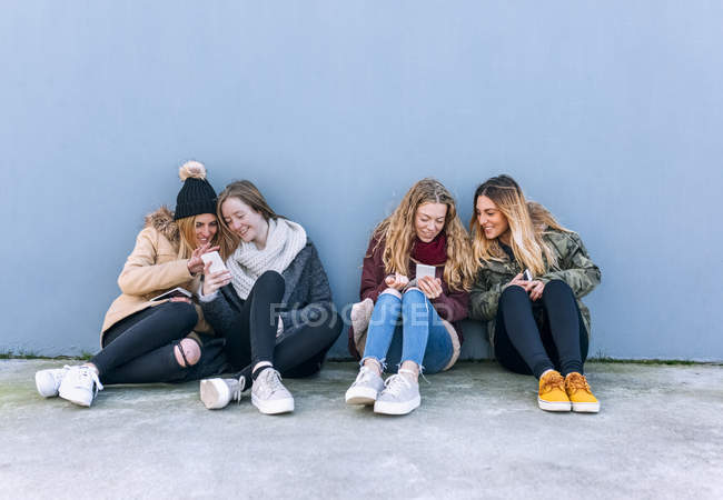 Four young women using smartphones in front of grey wall — Stock Photo