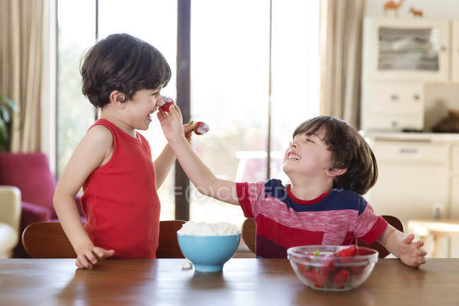 Twin brothers playing with strawberries — Stock Photo