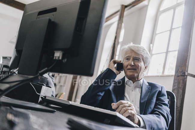 Retrato de homem de negócios sorrindo usando telefone à mesa — Fotografia de Stock