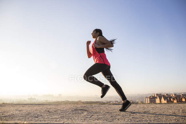 Young woman running on path in city — Stock Photo