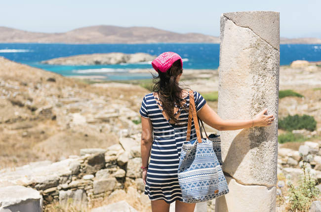 Delos, Mykonos, Greece.  Woman ejoying the view of The island of Delos, one of the most important mythological, historical and archaeological sites in Greece. — Stock Photo