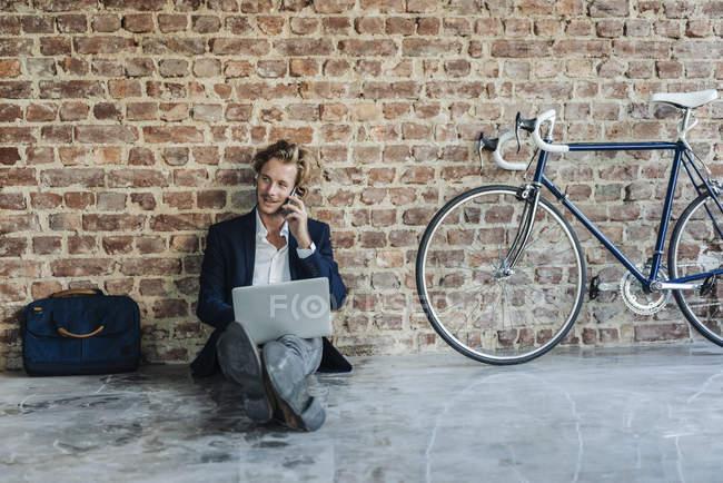 Uomo d'affari seduto sul pavimento e utilizzando laptop con telefono cellulare — Foto stock