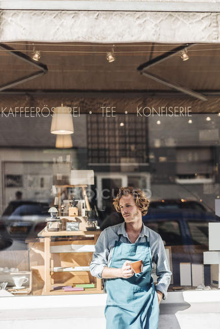 Coffee roaster holding cup in front of shop — Stock Photo