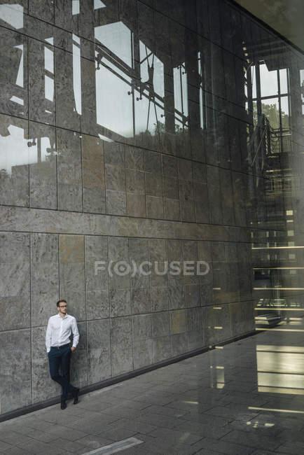 Ritratto di uomo d'affari in piedi vicino al muro di costruzione — Foto stock