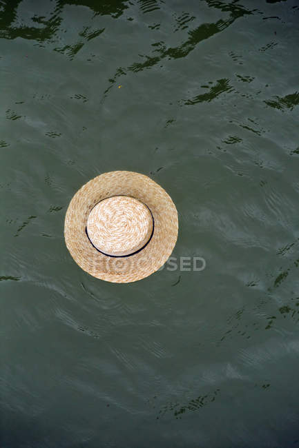 Straw hat floating on water surface — Stock Photo