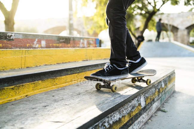 Skater boy riding skateboard in park, low section view — Stock Photo