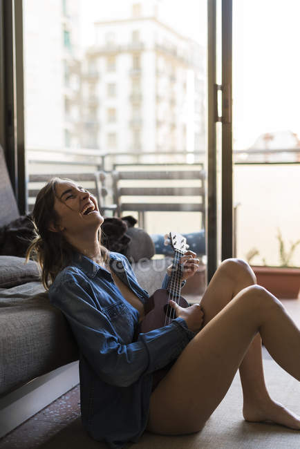 Young woman playing ukulele at home — Stock Photo