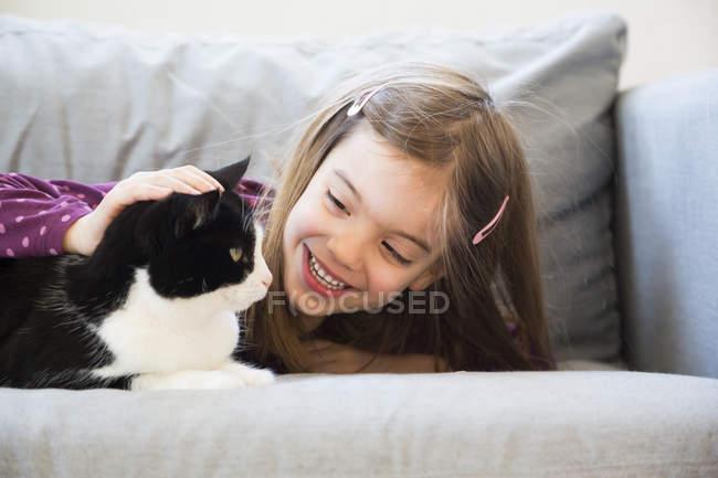 Niña acostada en el sofá y acariciando gato - foto de stock