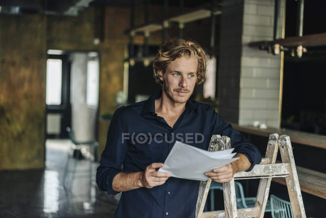 Man leaning on ladder in unfinished room and holding documents — Stock Photo
