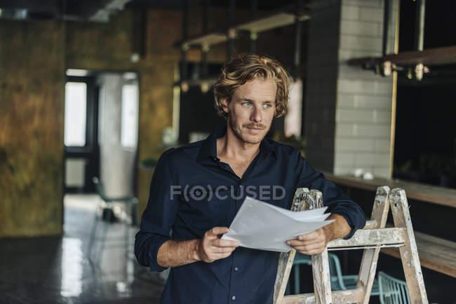 Uomo che si appoggia sulla scaletta in camera incompiuta e titolari di un documento — Foto stock