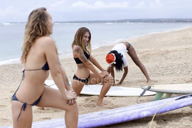 Индонезия, Бали, три женщины с досками для серфинга на пляже — стоковое фото