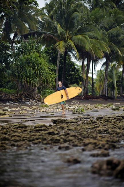 Індонезія, Java, людина, несучи для серфінгу на узбережжі — стокове фото
