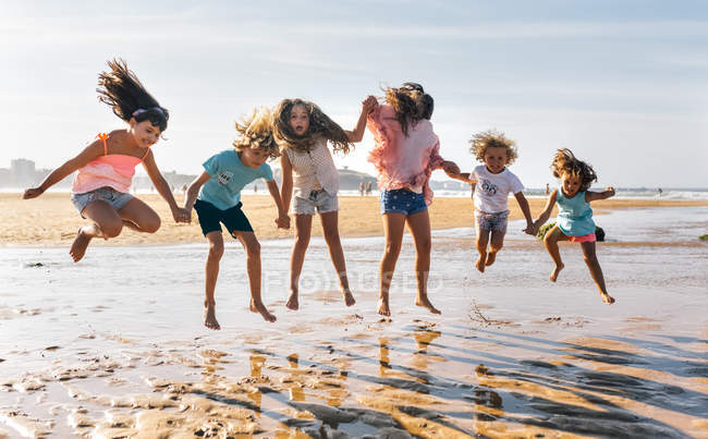 Group of kids jumping on the beach, Gijn, Asturias, Spain — Stock Photo