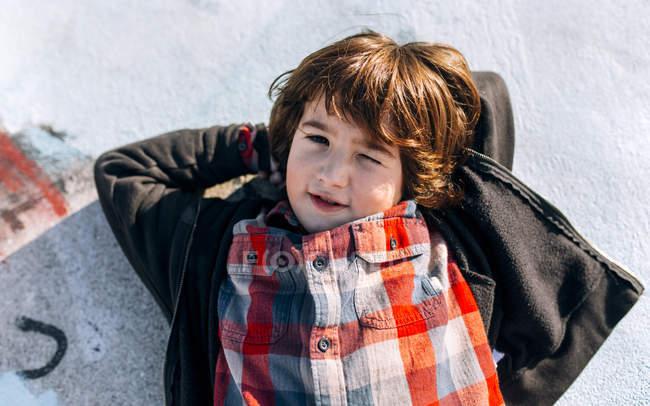 Netter kleiner Junge liegt auf dem Boden und schaut in die Kamera — Stockfoto