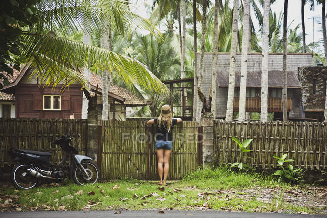 Indonesia, Java, woman leaning on garden gate looking at houses ...
