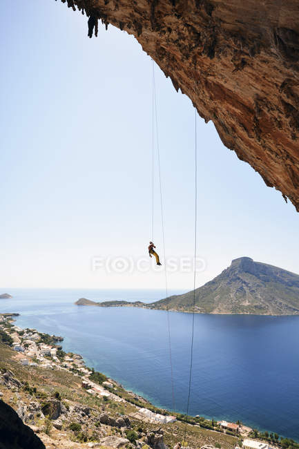 Daytime view of climber hanging on rope under rock — Stock Photo