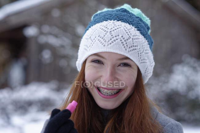 Портрет счастливой девочки-подростка с бальзамом для губ — стоковое фото