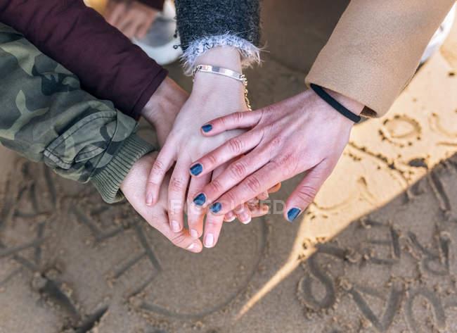 Gijn, Asturias, Spain, four friends jointing hands — стоковое фото