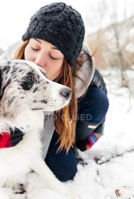 Leon, Spain, young beautiful woman giving a kiss to her dog in the snow — Stock Photo