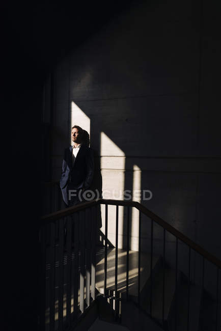 Portrait of businessman standing on staircase in shadows — Stock Photo