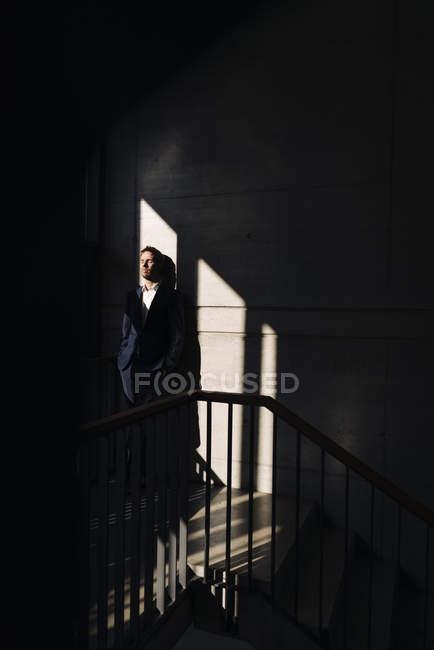Retrato do empresário em pé na escada nas sombras — Fotografia de Stock