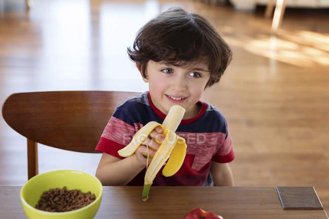 Мальчик сидит на стол завтрак и ест банан — стоковое фото