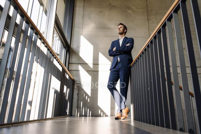 Vue de dessous d'homme d'affaires permanent sur l'escalier — Photo de stock