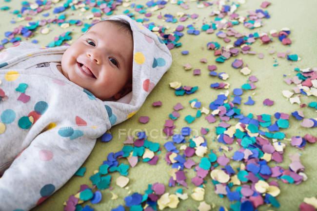 Щаслива дівчинка, оточені барвистими конфетті — стокове фото
