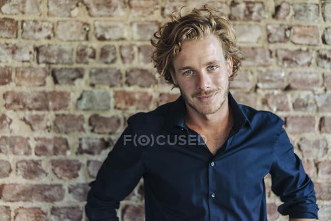 Portrait d'un homme souriant debout devant un mur de briques — Photo de stock