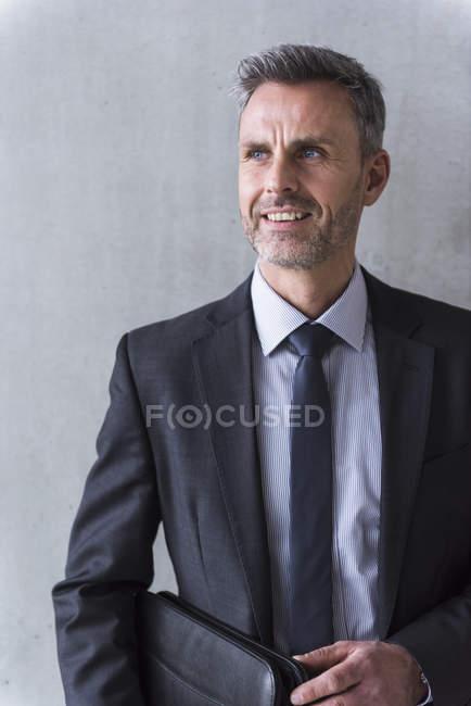 Бізнесмен, що стоїть перед сірих стін — стокове фото