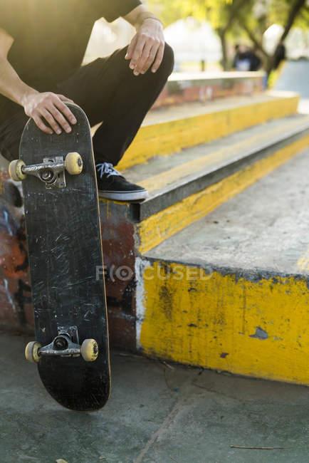 Фігурист хлопчика, що тримається низький розділ скейтборд — стокове фото