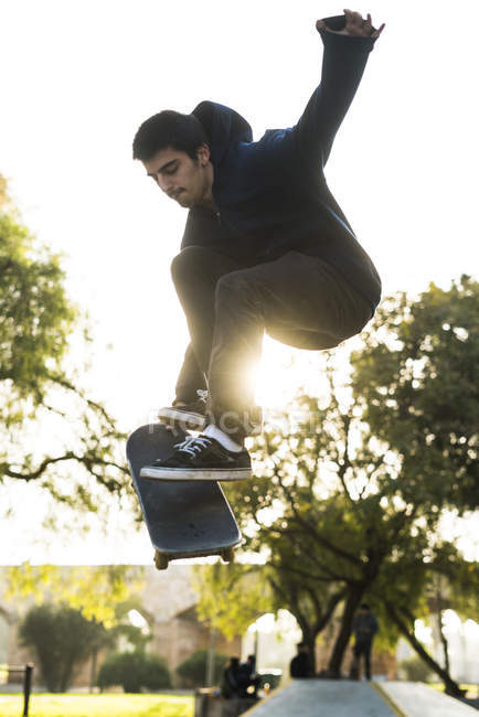 Skater boy tricking on skateboard, backlit — Stock Photo