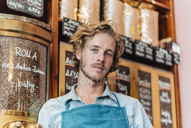 Portrait of coffee roaster standing in shop and looking at camera — Stock Photo