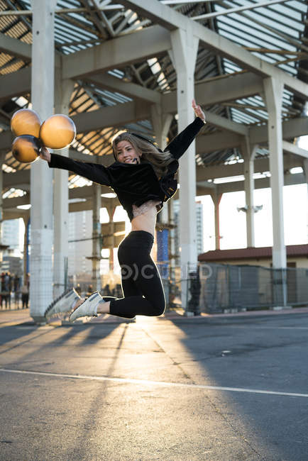 Young woman jumping with air baloons — Stock Photo